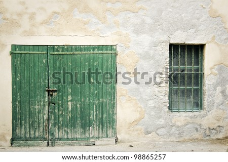 old green wooden door padlocked closed set in crumbling old wall with exposed bricks in the south of france - stock photo