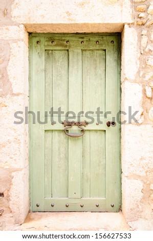 Old green wooden door with steel door knocker in thick stone wall - stock photo