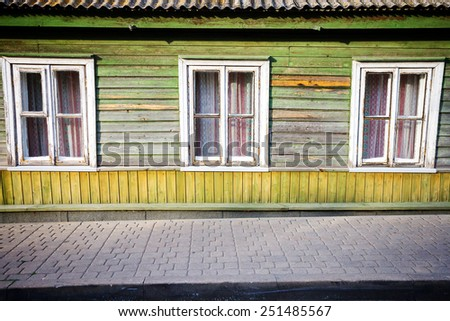 Old green wooden plank wall with some windows - stock photo