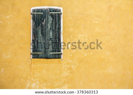 Old Green wooden window on the yellow facade - stock photo