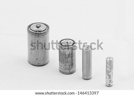 Old grey batteries on white background (aa, aaa, b, c) - stock photo