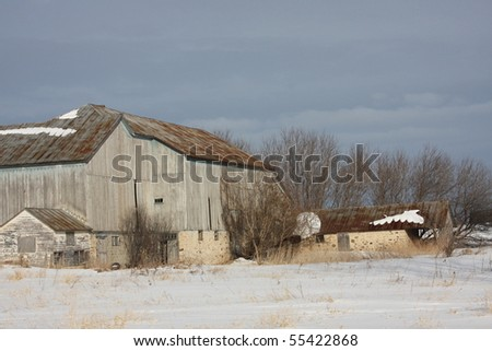 old grey Wisconsin dairy barn in winter - stock photo