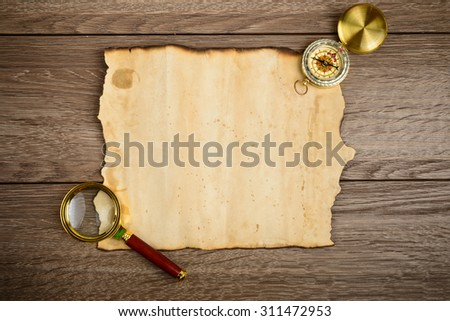 Old grunge blank paper sheet with compass and glass - stock photo
