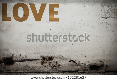 "Old grunge metal wall with the word  ""Love"". Background photo. - stock photo"