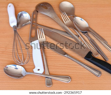 Old grunge steel kitchen utensils on wood background - stock photo