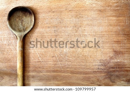Old grunge wooden cutting kitchen desk board with spoon background - stock photo
