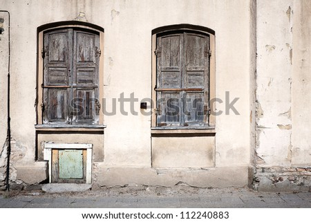 Old grungy wall with closed windows - stock photo