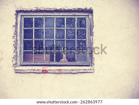 Old grungy window on an old dirty wall, retro filtered. - stock photo