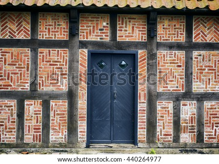 Old half-timbered  brick wall house with a blue door - Denmark - stock photo