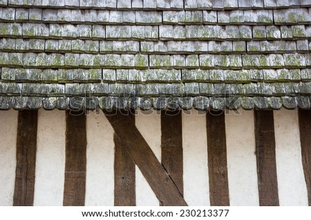 Old half timbered house house wall with traditional wooden tiled roof. - stock photo