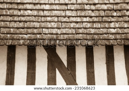 Old half timbered house house wall with traditional wooden tiled roof. Aged photo. Sepia. - stock photo