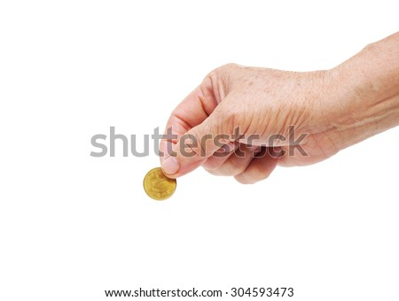 old hand of female elderly holding a golden coin - stock photo