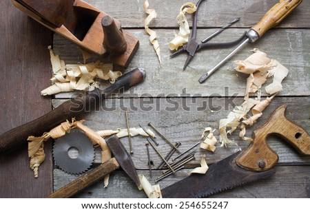 Old hand tools table upper view. Old rusty and dirty carpenter`s hand tools lying on wooden table with sawdust. - stock photo