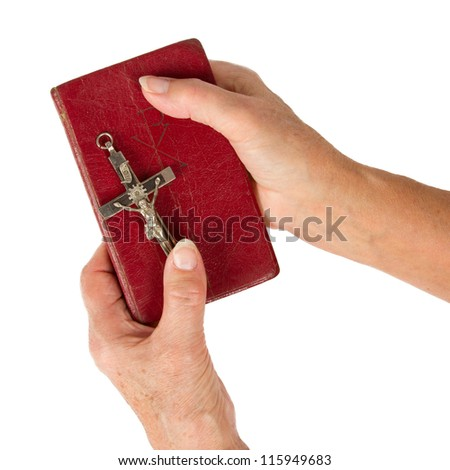 Old hands (woman) holding a very old bible, isolated on white - stock photo