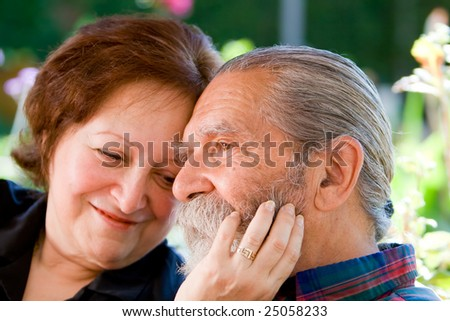 Old happy loving couple showing affection during retirement at their home - stock photo