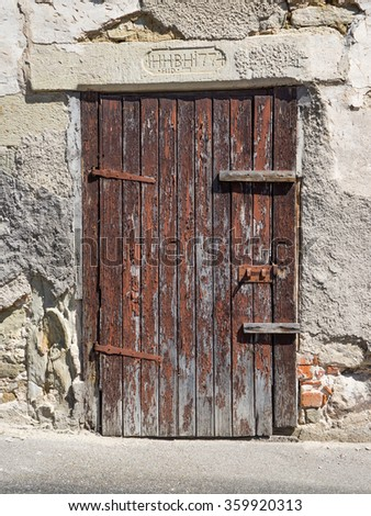 Old, heavily weathered, brown wooden door in the gray, dilapidated facade of an old building  - stock photo