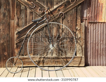 Old High Wheeled Bicycle Tied up in Front of Weathered Barn Door - stock photo