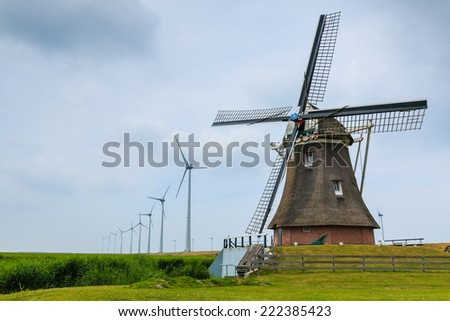 Old historic dutch windmill in the foreground and new windmills generating sustainable energy in the background. Eemshaven, Groningen, The Netherlands. - stock photo