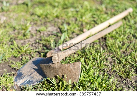 Old hoe and shovel on the grass and weeds. - stock photo