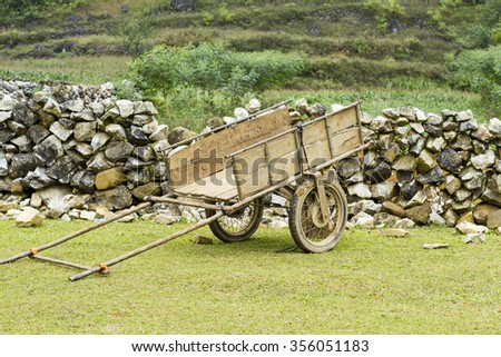 Old horse drawn wooden cart on grass field and stone wall behind in Vietnam - stock photo