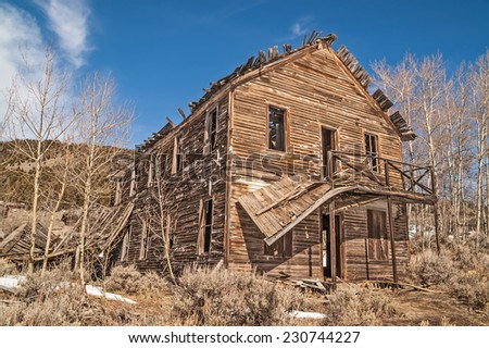 Old hotel in a Montana ghost town is losing its balcony and roof to time and neglect. - stock photo