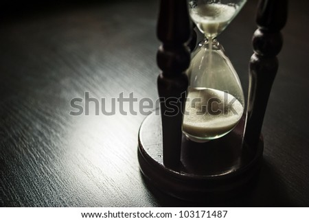 Old hourglass stand on a dark wooden table. - stock photo