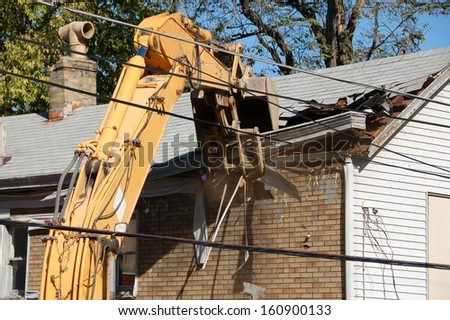 old house being demolished by a large backhoe - stock photo