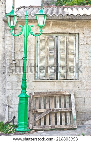 Old house in Greece with wooden shutters and a green lamp post - stock photo