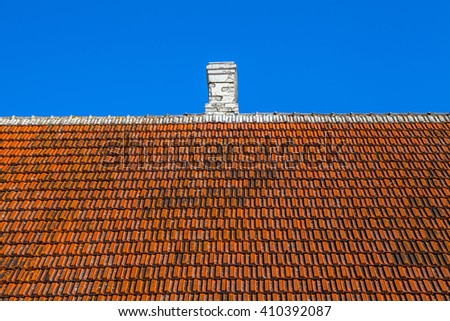 Old house tiled roof with white chimney - stock photo