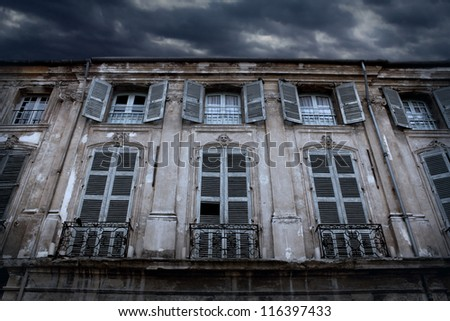Old house with gray shutters and thunder clouds in the sky. - stock photo