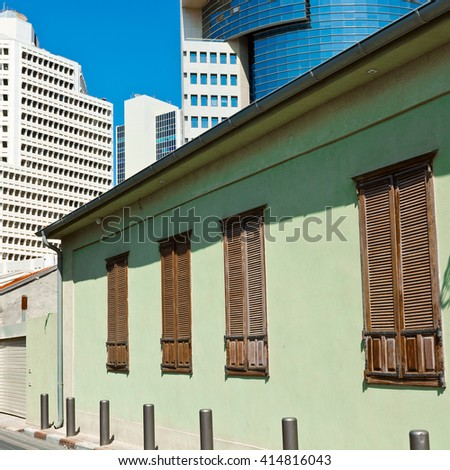 Old Houses after Reconstruction in Tel Aviv on the Background of the Modern Building - stock photo