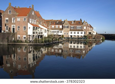 Old houses reflecting in the water in the small Dutch harbor town of Enkhuizen - stock photo