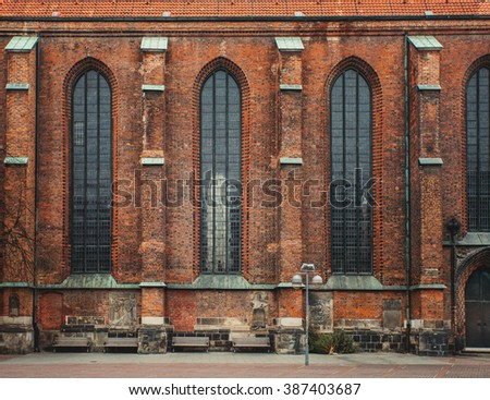 Old huge gothic building wall. Tall windows. Brickwork. Vintage effect.  - stock photo