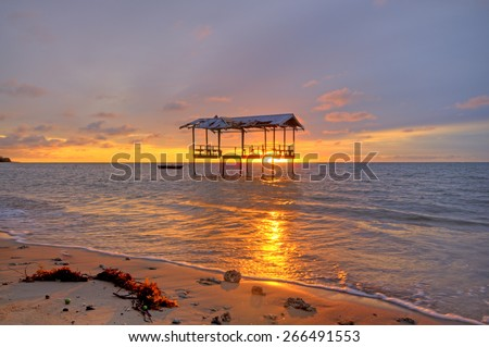 old hut with effect blur during sunset moment at kuala penyu, borneo sabah, malaysia Image has grain or blurry or noise and soft focus when view at full resolution.  (Shallow DOF, slight motion blur) - stock photo