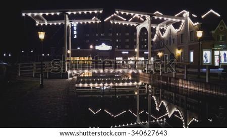 Old illuminated wooden bridge reflecting in canal - stock photo