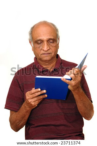 Old Indian Immigrant reading a blue book - stock photo