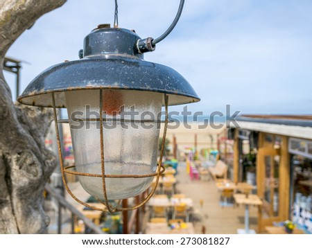 old industrial lamp with beachclub and sea in the background - stock photo