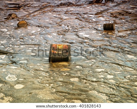 Old industrial metal barrels surrounded by contaminated environment. - stock photo