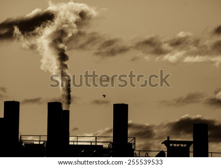 Old industrial site polluting the air with dark smoke. - stock photo
