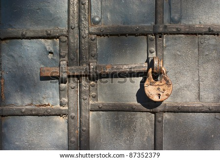Old iron door closed by the rusty lock - stock photo