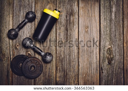 Old iron dumbbells or exercise weights with extra plates on an old wooden deck, floor or table. Image taken from above, top view. A lot of copy space around product. Horizontal image. - stock photo