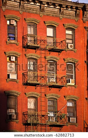 old iron fire escape rescue ladders at old houses in beautiful light - stock photo