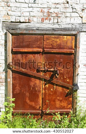 Old iron rusty door with  bolt on an ancient brick wall - gated entrance to the basement - stock photo