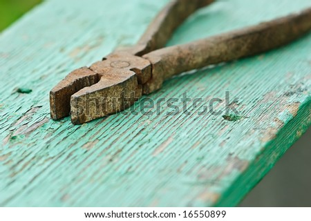 old iron rusty pliers with blurred background - stock photo