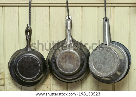 Old iron skillets and antique pans hang on hooks against a wall. - stock photo
