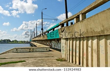 Old island bridge with graffiti in Riga. - stock photo