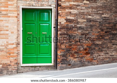 Old Italian architecture details. Green wooden door in old brick wall, background photo texture - stock photo