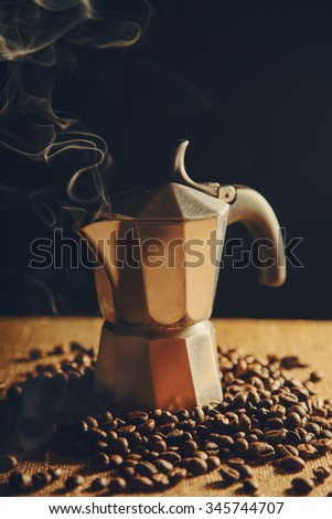 Old Italian coffee maker with coffee beans on canvas background  - stock photo