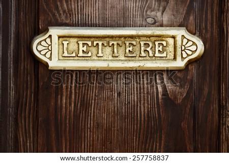 Old Italian letter box on wooden door  - stock photo