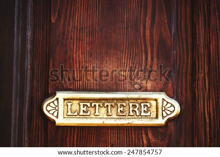 Old Italian letter box with wooden door background - stock photo